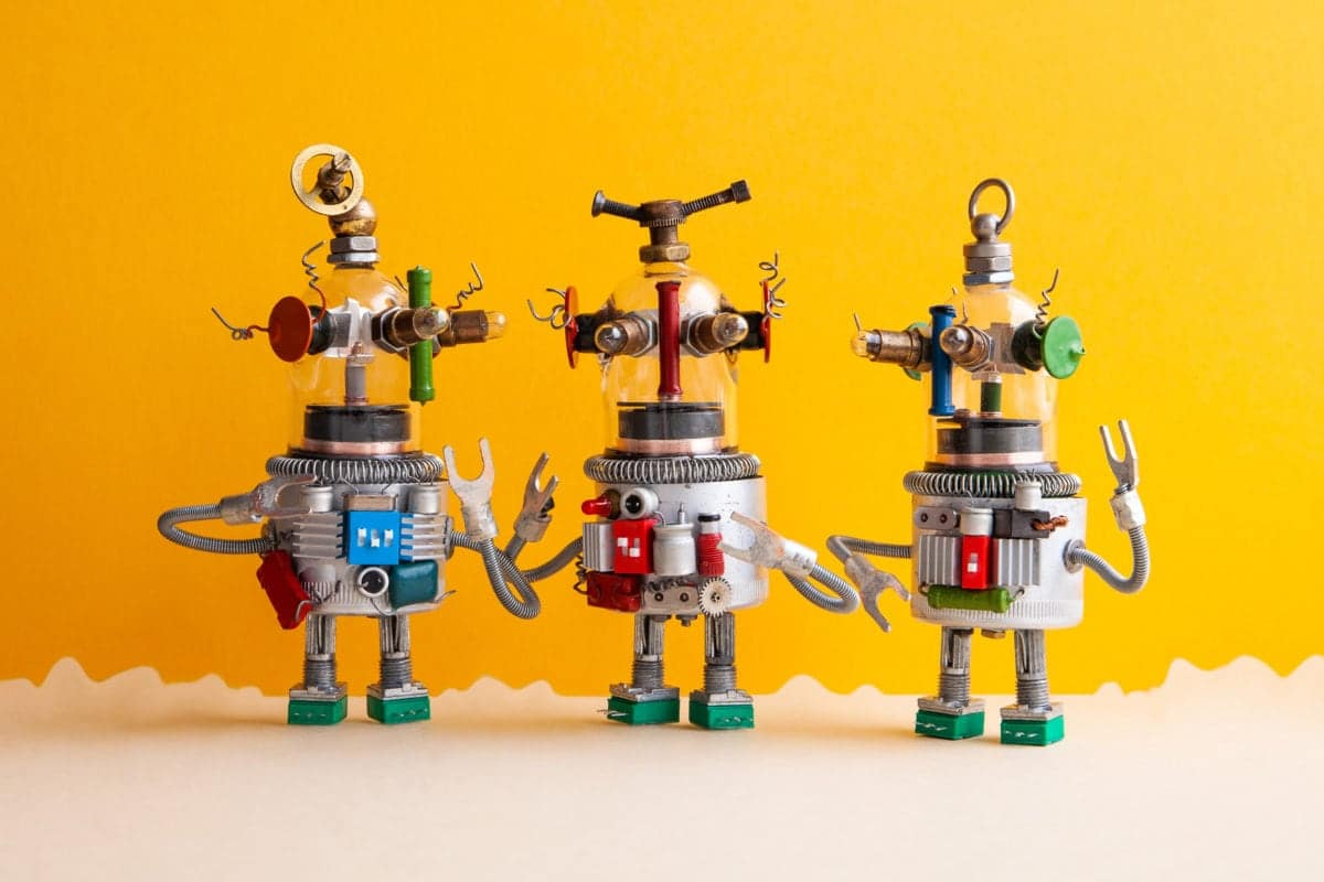 Funny glass headed ufo robots on a fantastic landscape. Three humanoid toy robots communicate. Yellow beige background.
