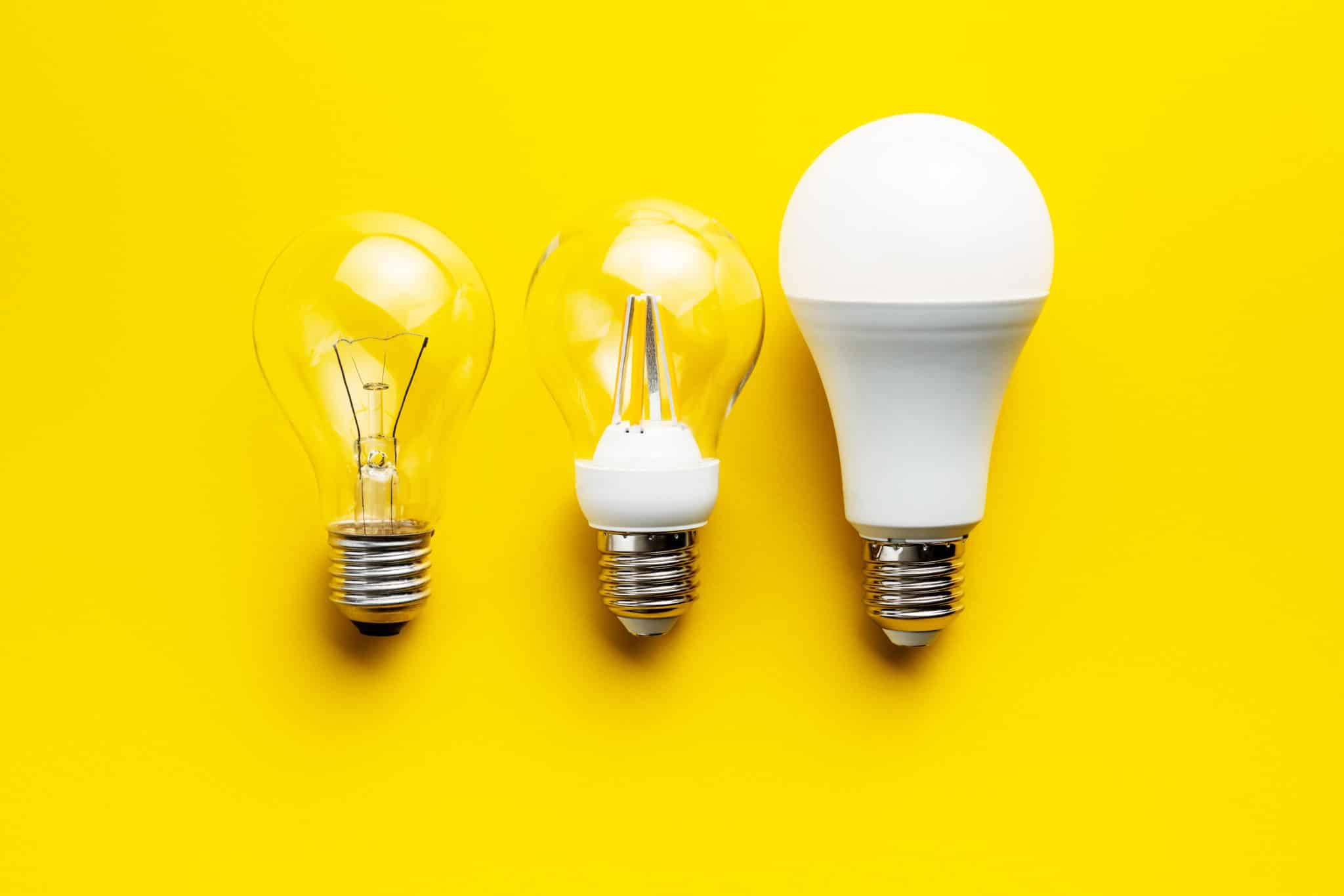 Energy saving and classic light bulbs on yellow background.