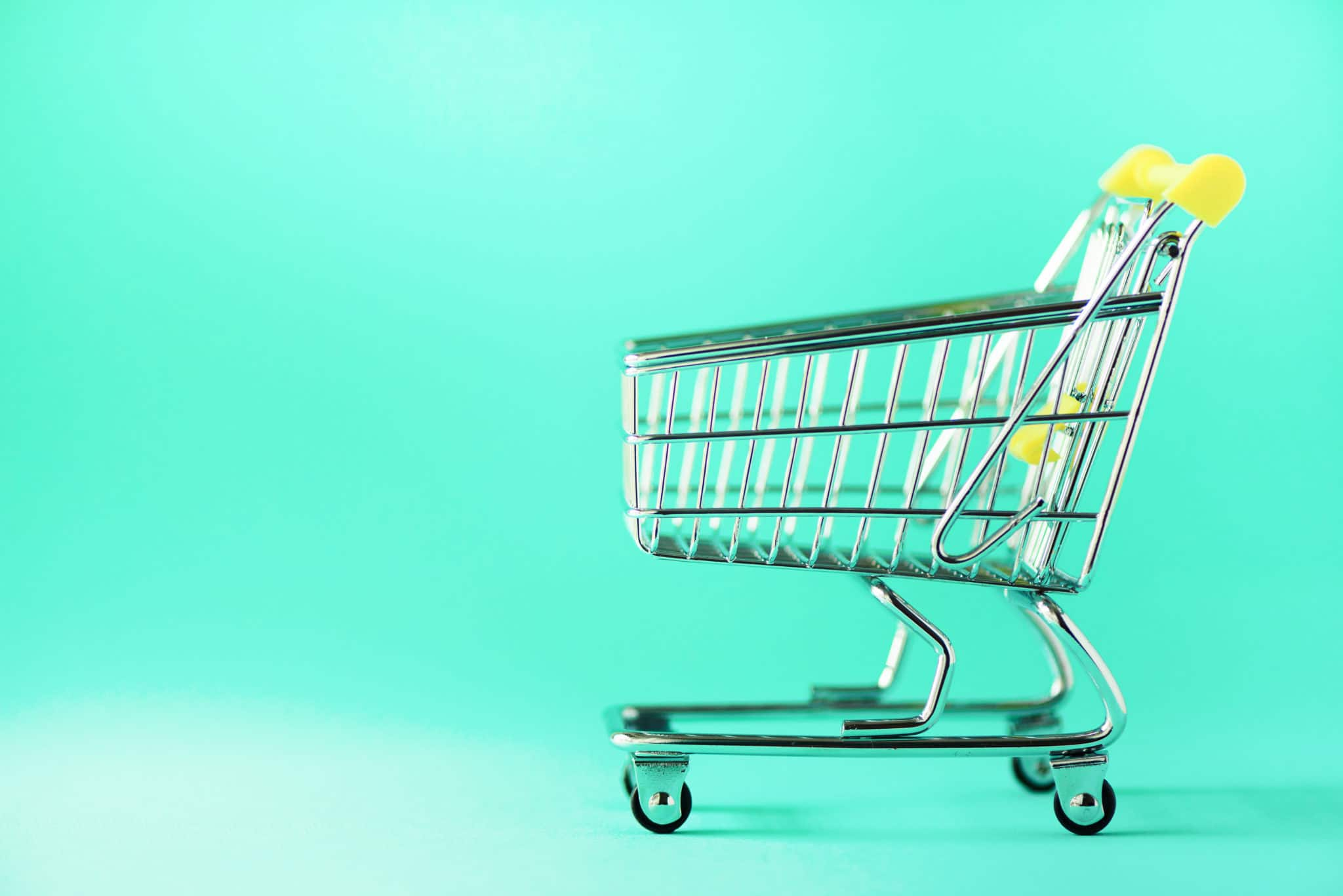 Shopping cart on blue background. Minimalism style. Creative design. Copy space. Shop trolley at supermarket. Sale, discount, shopaholism concept. Consumer society trend.