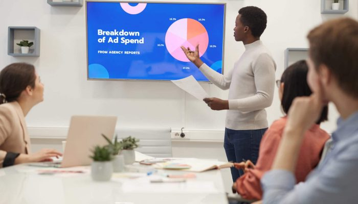 Portrait of young African businessman pointing at marketing data chart while giving presentation during meeting in modern office, copy space
